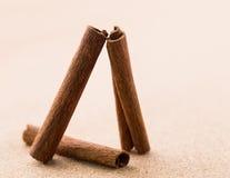 Tres palillos de canela en fondo del corkwood. Fotos de archivo libres de regalías