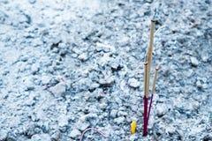 Tres palillos del incienso y una vela están quemando en el pote w del incienso Imagen de archivo libre de regalías