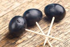 Tres palillos en los cuales están las bayas atadas de la uva, viejo fondo de madera natural foto de archivo