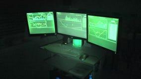 Tres pantallas de ordenador de los comerciantes de Bitcoin almacen de metraje de vídeo