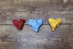 Tres papeles arrugados en forma de corazón coloridos en la tabla de madera ` S de la tarjeta del día de San Valentín Día del ` s  Imagenes de archivo