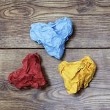 Tres papeles arrugados en forma de corazón coloridos en la tabla de madera ` S de la tarjeta del día de San Valentín Día del ` s  Imagen de archivo libre de regalías