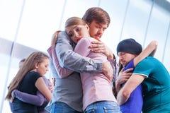 Tres pares de gente que se abraza. imagenes de archivo
