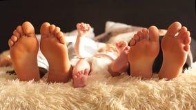 Tres pares de piernas de la familia feliz en cama debajo de la sobrecama metrajes