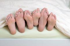 Tres pares de pies en cama Imagenes de archivo