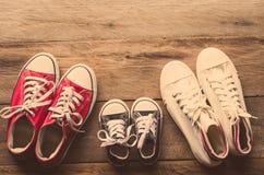 Tres pares de zapatos ponen en el piso de madera de la familia, de los padres y de los niños para hacer juntos imagenes de archivo