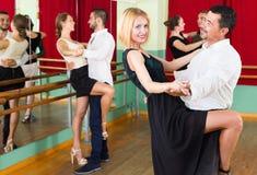 Tres pares felices que bailan tango Imagen de archivo libre de regalías