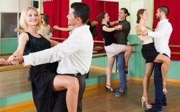 Tres pares felices que bailan tango Imágenes de archivo libres de regalías