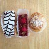Tres pasteles que se sientan en una tabla fotografía de archivo libre de regalías