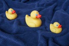Tres patos de goma amarillos en la toalla ondulada azul imagenes de archivo