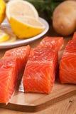 Tres pedazos de color salmón en una tajadera Imagen de archivo