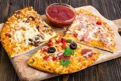 Tres pedazos de diversas pizzas en un de madera Imagenes de archivo