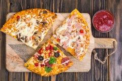 Tres pedazos de diversas pizzas en un de madera Fotos de archivo libres de regalías