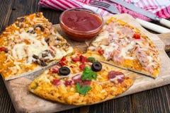 Tres pedazos de diversas pizzas en un de madera Fotografía de archivo