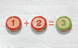Tres pedazos de madera que representan la adición del número uno y dos Fotos de archivo libres de regalías