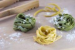 Tres pedazos de pastas amarillas y verdes en la tabla fotografía de archivo
