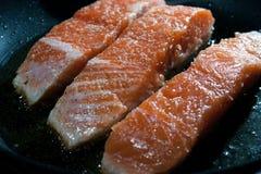Tres pedazos de salmones cocinados en aceite Imagenes de archivo