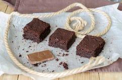 Tres pedazos del brownie y chocolate quebrado en el papel de la hornada Imagen de archivo libre de regalías