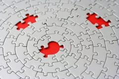 Tres pedazos que falta en un rompecabezas gris Imágenes de archivo libres de regalías