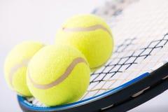 Tres pelotas de tenis y una raqueta Imagen de archivo libre de regalías