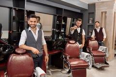 Tres peluqueros hermosos que presentan en barbería cerca de sillas del peluquero fotos de archivo