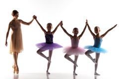 Tres pequeñas bailarinas que bailan con el profesor personal del ballet en estudio de la danza imagen de archivo