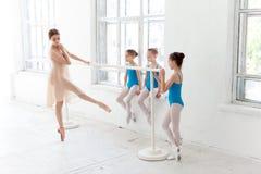 Tres pequeñas bailarinas que bailan con el profesor personal del ballet en estudio de la danza Foto de archivo libre de regalías