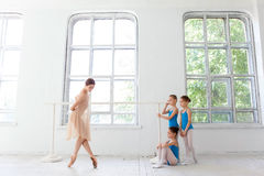 Tres pequeñas bailarinas que bailan con el profesor personal del ballet en estudio de la danza Foto de archivo