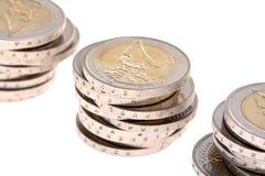 Tres pequeñas columnas de las monedas dos-euro aisladas Imágenes de archivo libres de regalías