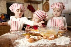 Tres pequeños cocineros en la cocina Fotografía de archivo