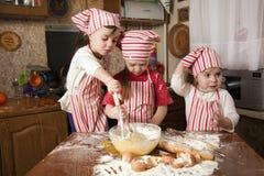 Tres pequeños cocineros en la cocina Imágenes de archivo libres de regalías