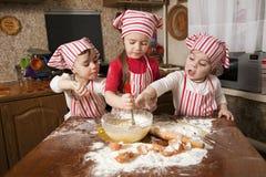 Tres pequeños cocineros en la cocina Fotos de archivo libres de regalías