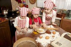 Tres pequeños cocineros en la cocina Imagen de archivo