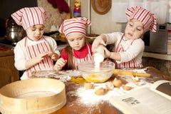 Tres pequeños cocineros en la cocina Foto de archivo
