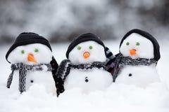 Tres pequeños muñecos de nieve con los sombreros Imagenes de archivo