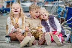 Tres pequeños niños felices se sientan en el embarcadero Imagen de archivo