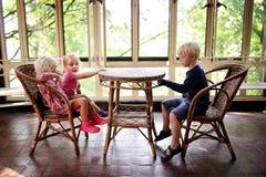 Tres pequeños niños que se sientan en una tabla vieja de los bistros en un Sunroo fotografía de archivo