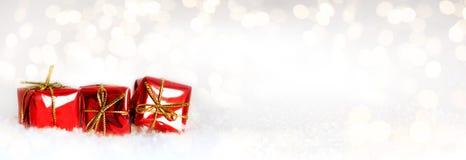 Tres pequeños regalos rojos en la nieve Fotografía de archivo