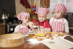 Tres pequeños cocineros la cocina Fotos de archivo libres de regalías