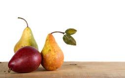 Tres peras en un tablón de madera Imagen de archivo