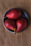 Tres peras rojas en la placa azul Fotografía de archivo