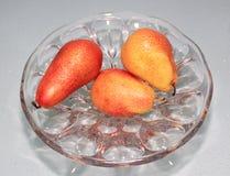 Tres peras rojas en un florero Imagen de archivo