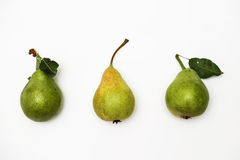Tres peras verdes maduras con una puntilla que miente en fila en un fondo blanco Visión superior Imagen de archivo