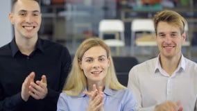 Tres personas aplauden feliz sus manos para expresar placer almacen de video