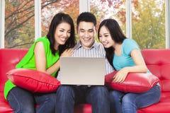 Tres personas asiáticas que usan el ordenador portátil Imagen de archivo libre de regalías