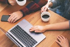 Tres personas asi?ticas jovenes que usan y mirando el mismo ordenador port?til durante una reuni?n imágenes de archivo libres de regalías