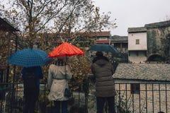 Tres personas con los paraguas Calle en Mostar imagenes de archivo