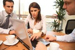 Tres personas del asunto que trabajan junto con la computadora portátil en oficina asoleada imagen de archivo libre de regalías