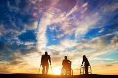 Tres personas discapacitadas en la puesta del sol Foto de archivo