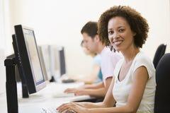 Tres personas en sala de ordenadores que pulsan y que sonríen Imagen de archivo